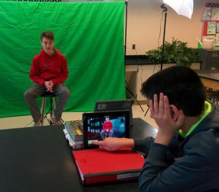JGMS students creating a video using green screen technology.