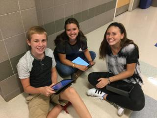 High School students working collaboratively with iPads to complete class assignments.